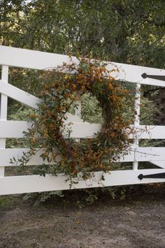 I love this Fall wreath hanging on the white fence, would be great on a door also!!