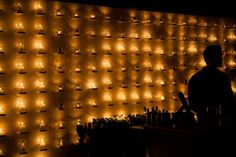 Candle wall behind bar, or as a bar back, created a glow effect that would be a great piece for any wedding.