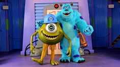 Mike and Sulley from Monsters, Inc. smile while standing together right outside Boo's closet door