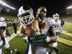 Lawrence Thomas carries the Paul Bunyan Trophy after their 27-23 over Michigan on Saturday in Ann Arbor.  Julian H. Gonzalez DFP
