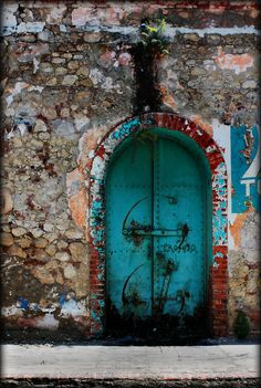 Jacmel, Haiti; most of the houses have walls and gates such as this brightly covered door.