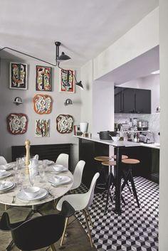 """La cuisine ouverte s'habille de marbre de Carrare et de meubles noirs. Dans le coin salle à manger, une table """"Tulip"""" de Saarinen, des chaises """"DSW"""" de Charles & Ray Eames et de la vaisselle d'Astier de Villatte. Derrière, sur le mur, toutes les couleurs des céramiques de Fernand Léger."""