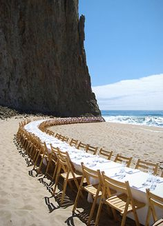 the setting is the centerpiece...awesome...beach table dinner..who needs more