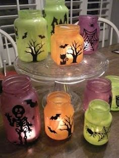 Halloween Luminaries (mix white glue and craft paint and paint the inside of glass jars; decorate outside of jar with vinyl cutouts; add candle)