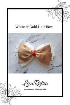 A stylish hand-crafted white and gold hair bow made from quality grosgrain and satin ribbons. Perfect for special ocassions such as christenings, weddings, birthday parties or photo shoots. Sparkly rhinestone embellishment and fancy white net/tulle. It has an uncovered alligator clip attached to the back so it can be placed securely in the hair. Approx length 3ins/8cm x Width 5.5ins/13.5cm Tulle Hair Bows, Girl Hair Bows, Gold Hair Bow, Tween Girl Gifts, Handmade Hair Accessories, Making Hair Bows, How To Make Bows, Large White, Homemade Business