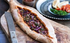 <p>This savory flat bread is made with a slightly spicy Harissa sauce, tangy tomato paste, black olives, and jalapeño, there is a ton of flavor in each bite. </p>