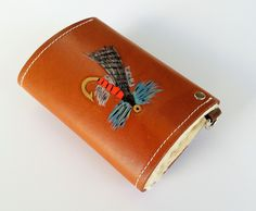 Custom Tooled Tan Leather Fly Fishing Wallet Case with Sheepskin Fleece Keep Flies Dry Ready to Ship. A hand tooled and colored leather Fly Fishing Wallet Case lined with sheepskin fleece. The case is designed to hold fishing flies and keep them dry. The closure is a sturdy #20 snap. The wallet leather is not only glued but also stitched to the sheepskin fleece. The sheepskin fleece will absorb the moisture from wet flies and keep them dry so they float. The leather has a water resistant...