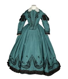 Dress.  France. 1863-1865.  Green silk trimmed with taffeta and a lace collar  Silk material is hand-embroidered in silk and cut-steel beads,