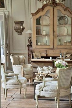 """COUNTRY vibe (1) unfinished wood used for the China cabinet & flooring (2) mismatched armchairs (3) """"collected"""" feel from eclectic furnishings - Baroque-inspired China cabinet, coffee table w/ metal legs, Rococo & Neo-Classic-inspired armchairs (4) checkerboard pattern & heavy linen in upholstery. CHIC vibe (1) classic details - Rococo, Neo-Classic, Baroque; wall paneling (2) China collection (3) chandelier (4) exposed nail heads. #country #chic #countrychic #classic"""