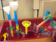 Experimenting with water, tubes and funnels in the water table-using a wire rack for support.....
