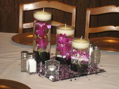 "Center piece with Purple orchids and glass gems in water, square votives and beaded garland on 12"" square mirror."