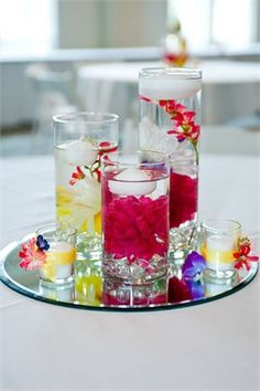 If you are lost for centrepiece ideas then why not put several vases on top of round mirrored plates and fill them with coloured stones, floating candles or flowers. Vases can be picked up inexpensively on the high street or from some of the major home interior stores. You can also decorate with tea lights to add a little bit of extra glimmer and shine to your tables.