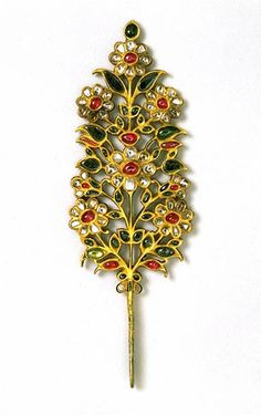 Turban ornament, India or Pakistan, early 18th century. Set with rubies, emeralds and pale beryls on one side, and the same stones with the addition of diamonds on the other. The stem and the sides of the jewel are enamelled in translucent green.