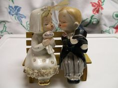 vintage salt and pepper shakers with kissing bride and groom sitting on a wood bench  -they are about 4 tall and in good condition  -there is