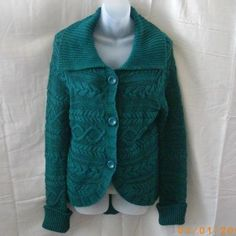 This new green Volcom cardigan has a large fold-back collar, three large buttons, long sleeves with deep ribbed cuffs, and a rounded hemline which dips in the back. The front and sleeves have cable detail, and the back is in garter-stitch knit....