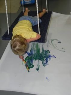 Combining painting with a platform swing ==> genius! Play at Home Mom shares tips and finished works Sensory Swing, Sensory Art, Autism Sensory, Multi Sensory, Sensory Rooms, Vestibular Activities, Motor Skills Activities, Gross Motor Skills, Pediatric Occupational Therapy