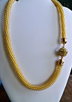 Elegant, sophisticated beaded Kumihimo necklace with a rhinestone studded magnetic clasp that can also be the focal pendant, depending on where you center it. See the various pictures for wear suggestions. The lightweight necklace is finished with gold plate end cones. It measures 20 inches / 50.88 cm long. The shimmering yellow/gold seed beads give off a warm, sun-shiney type glow.  All necklaces contain the Beckoning Cat tag.  The ancient Kumihimo braiding process (dating back to the days…