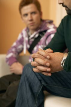 Father sitting with teenage son