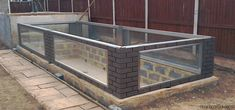 large bolt together instant pond. brick and stainless steel with windows