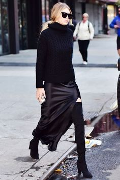 """This isn't your typical black-from-head-to-toe #OOTD. Hadid trades the skinny jeans for a silk maxi-skirt with a high slit, and swaps the tattered T-shirt for a chunky turtleneck. (Both are Nili Lotan.) Instead of the customary ankle boots, the model opts for drama and shows a sliver of skin, thanks to the aforementioned slit, with Stuart Weitzman's aptly named """"All Legs"""" over-the-knee boots. Photo: Getty Images"""