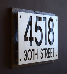 Custom Stainless Steel House Number Address Plaque cut/finished/ mounted over a piece of Natural Slate or Cedar -2 Line size (8x16) accommodates both house numbers, and street name, or last name. -Durable, Maintenance free Stainless Steel plate suitable in any environment, -Ultra
