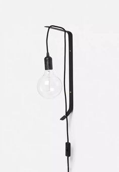 Add a warm glow to your cosy reading nook with this wall-mounted lamp. The exposed bulb has an on-trend, Scandinavian feel and a hanging effect is created due to the cord being threaded through the frame. Place it separately or buy two to use as bedside lights. Bulb included.