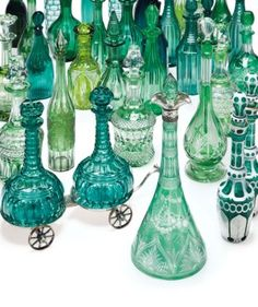 A COLLECTION OF TWENTY-THREE GREEN GLASS DECANTERS