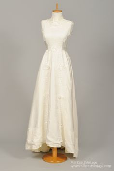 Designed in the 50's, this magnificent vintage wedding dress is done in a beautiful creamy lace embroidered taffeta over a muslin lining. The sleeveless bodice offers a high mock collar and lace embro