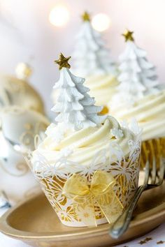 White and gold cupcakes decorated with Christmas tree icing Photo by RuthBlack on Getty Images