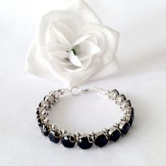 This 7.25 inch Black Sun tennis bracelet and 1.75 inch earring set features a series of 2 carat diamond cut jet black Cubic Zirconia with sterling silver embellishments and findings.