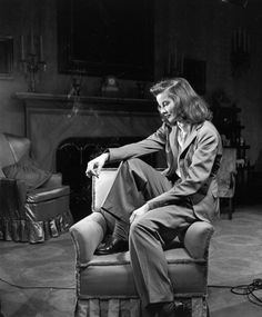 Portrait of actress Katharine Hepburn sitting on arm of chair, smoking. Photo by Alfred Eisenstaedt
