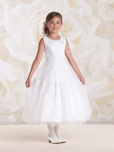 Sleeveless satin and tulle tea-length A-line dress with hand-beaded scoop neckline, satin bodice with Chantilly lace overlay, natural waist accented with scalloped edge lace appliqué, covered buttons down back, full gathered tulle and Chantilly lace dirndl skirt with scalloped edge, ideal as a First Holy Communion dress. Sizes: 6 – 14