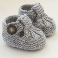 These cute little T-bar shoes have been knitted using lovely Sirdar wool blend yarn in silver grey.    They are fastened with mottled grey and brown buttons. They are light and comfortable. Just right for wearing in the buggy or car seat. An ideal Baby...