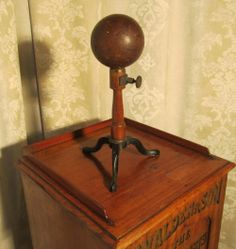 19th Century Wig Makers Stand The sphere is made of solid wood.  Brass spindle and screws mounted on a wooden stand which has a cast iron tripod base.