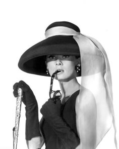 Audrey Hepburn as Holly Golightly. I knew this was a reason I always do that with my sunglasses :)