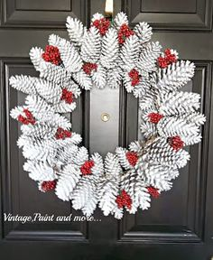 White pinecone wreath with red berry accents.