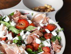 Deze zomerse salade met aardbei, geitenkaas en parmaham is nu al erg lekker om te eten maar straks in de zomer een waar feestje op tafel.