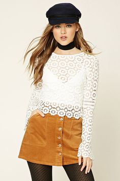 A woven corduroy mini skirt featuring a button-down front, front slanted patch pockets, and front buttoned belt loops.