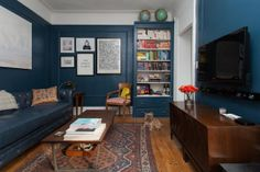 Drawn to the dark blue and traditionalish rug. Not really related, but makes me think of the way I imagined the captain's home in Cornwall in Susan Cooper's books - although that would be darker and more masculine.