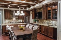 There's plenty of seating and space in this grand, eat-in kitchen. Custom wood cabinets and a stacked stone backsplash adds a warm and rustic feel. A large wood dining table fits a great deal of luxurious seating, creating a space that is not only elegant but great for entertaining.