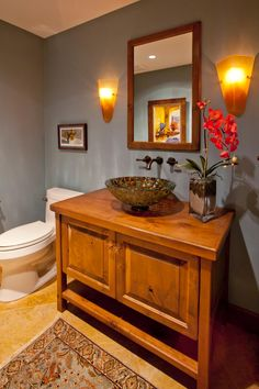 The warm, low light and gray walls in this craftsman powder room create a relaxing feel. Tulip-shaped sconces are mounted above the wooden vanity highlighting the beautiful reflective colors of the mosaic vessel sink. A patterned rug adds more warm color tones atop the neutral marble flooring.