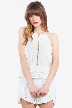 """An amazing eyelet halter romper with the cutest details. Wear it during festival season paired with gladiator sandals and a floppy hat.   - Eyelet peplum halter romper - Wrap shorts - Cotton lace trim in the front and back - Tassel trim - Stretch band at waist  Size + Fit - Model is wearing size S - Measurements taken from size S - Waist: 25.5"""" - Chest: 31"""""""
