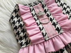 Simply gorgeous! This Chanel inspired, houndstooth print dog harness is an elegant addition to your fur babys collection. Accented with pink ruffles and a pearl/ rhinestone tiara button. Harness comes with a D-ring and Velcro closure on neck and belly. Check out this other