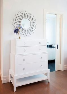 Chic bedroom boasts a stacked white dresser, Bungalow 5 Pandora Tall 4 Dresser, placed under a white mirror.
