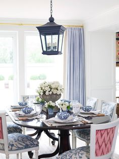 Gorgeous lilac dining room with sliding doors covered in lilac curtains window panels, iron lantern, glossy dining table and French square back dining chairs upholstered in blue & pink fabric.