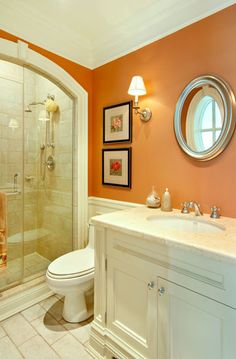 Warm orange and creamy white bathroom with white countertop. Gorgeous.
