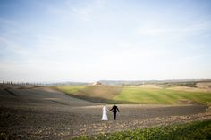 Walking the fields on the tucany countryside just after their wedding - more tuscany wedding photos at: www.weddingphotos.it