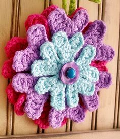 Layered crochet flower with BUTTONS that hangs on an adorable bead-board door; $28; feltedbutton.com