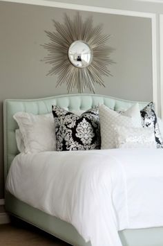 White bedding, gray wall, mint green tufted headboard.