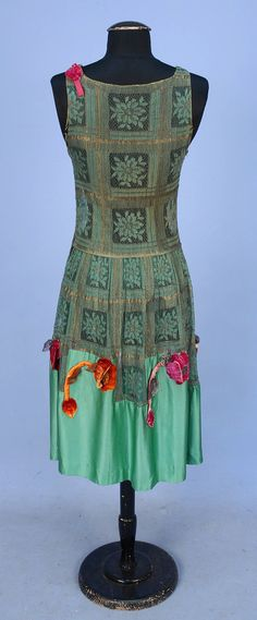 LACE EVENING DRESS with FLORAL APPLIQUE, 1920's. Sleeveless green and gold metallic lace having floral blocks, lower skirt of jade green silk charmeuse appliqued with velvet poppies. Back